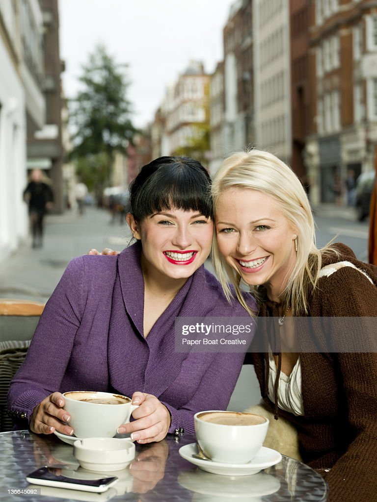best friends sitting by the cafe having cappucino : Stock Photo