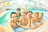 Best friends taking selfie in swimming pool - Happy friendship concept with young people having fun together - Warm vintage filter with soft focus on faces due to natural lights and backlight contrast