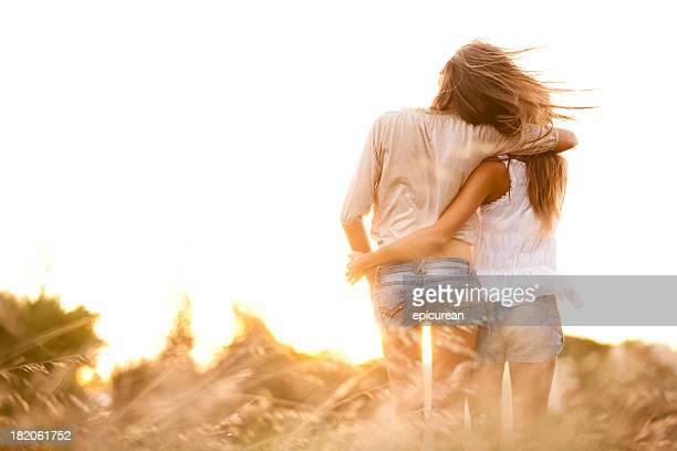 Meilleurs amis en regardant le coucher de soleil et s'enlacer