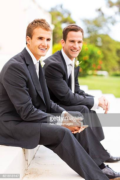 Best Man And Groom Sitting Together In Garden