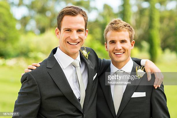 Best Man And Groom Standing Together In Garden