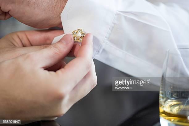 Best man closing cufflink at grooms shirt