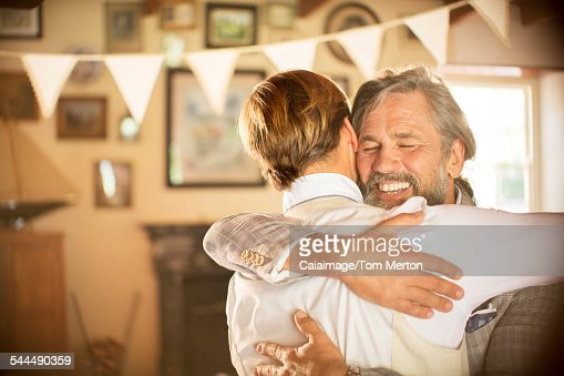 Best man embracing bridegroom in domestic room