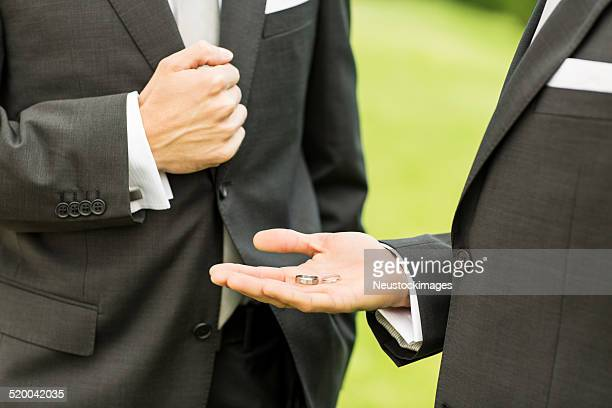 Best Man Showing Wedding Rings To Groom