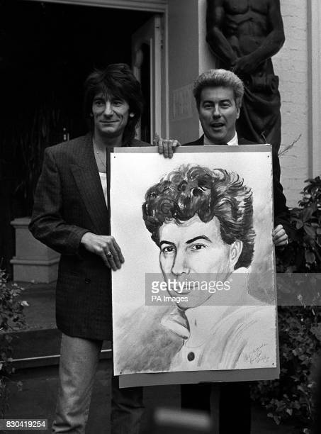 Best selling author Ken Follett is given a portrait of himself by the artist Rolling Stone guitarist Ron Wood in London at a preview of his first...