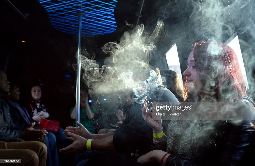 Beth Bice of Charlotte, NC smokes a joint on the bus during a marijuana tour hosted by My 420 Tours in Denver, CO on December 06, 2014. Bice saw a video advertising the tours and said, 'lets go to Colorado.' She explained, 'Im not a big drinker. So to do this and find people like me it feels awesome. Its a movement, you want to be a part of it. The more and more people that get on board with this, the more and more acceptable it will become. During the day tourists visited La Conte's grow facility, La Conte's Clone Bar & Dispensary, Native Roots dispensary and Illuzions Glass Gallery.