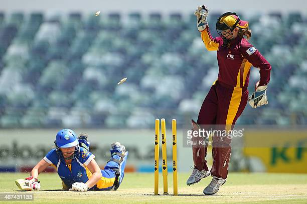 Beth Mooney of the Fire removes the bails as Sara Hungerford of the Meteors makes her ground during the WT20 Final match between Queensland and the...
