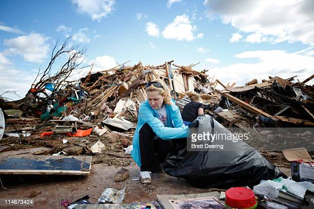Beth Parrett sifts through the debris of her home that was struck by a tornado May 25 2011 in Piedmont Oklahoma The state medical examiner's office...