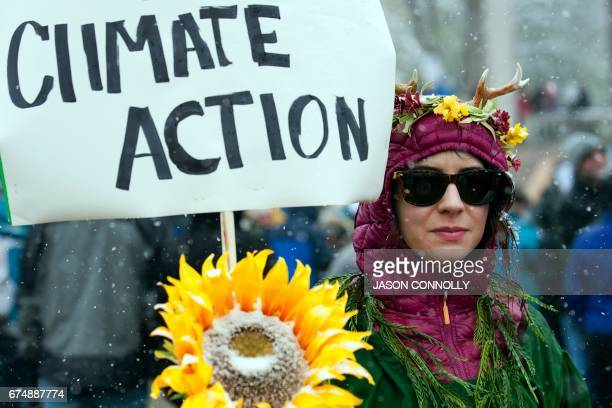 TOPSHOT Beth Phuxster of Denver Colorado dressed as Mother Nature holds a sign while participating in the People's Climate March during a spring snow...