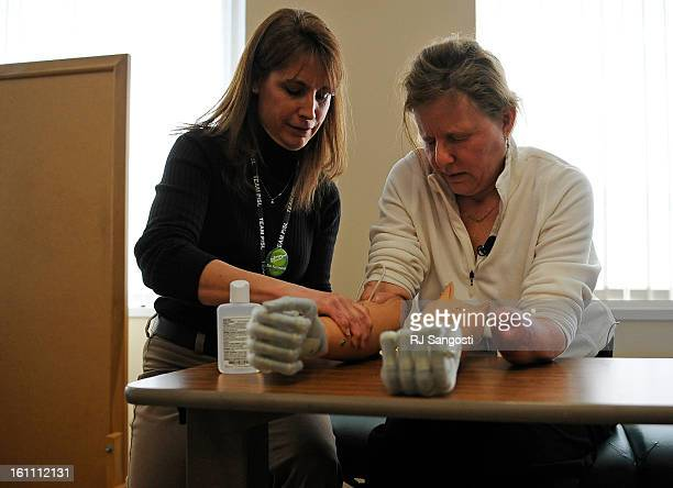 Beth Rayas who lost all four limbs to sepsis works with her new iLimb hands with Occupational Hand Therapist Julie Klarich left Thursday Jan 06 at...