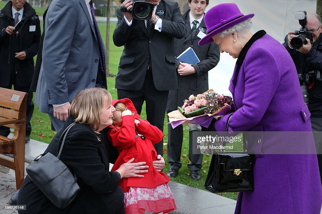 Bethany Wiles aged three covers her face and is held by her mother Rae Wiles (L) after giving flowers to Queen <a gi-track='captionPersonalityLinkClicked' href=/galleries/search?phrase=Elizabeth+II&family=editorial&specificpeople=67226 ng-click='$event.stopPropagation()'>Elizabeth II</a> at the opening of the recently re-built Jubilee Gardens on October 25, 2012 in London, England. The recent transformation of the Jubilee Gardens was completed 35 years after they were first created in 1977 to celebrate The Queen's Silver Jubilee.
