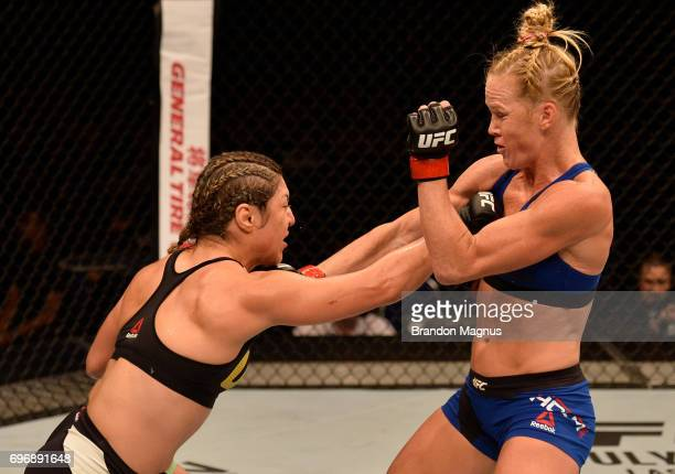 Bethe Correia of Brazil and Holly Holm trade punches in their women's bantamweight bout during the UFC Fight Night event at the Singapore Indoor...