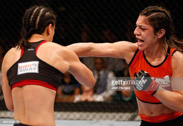 Bethe Correia of Brazil punches Shayna Baszler in their women's bantamweight bout during the UFC 177 event at Sleep Train Arena on August 30 2014 in...