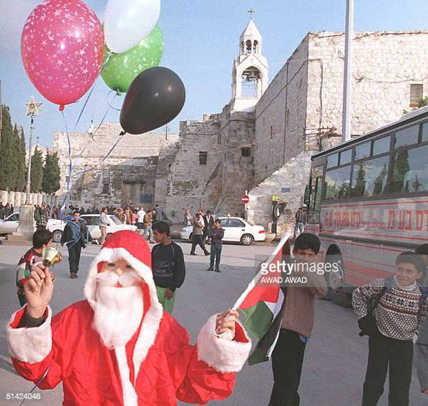 Palestinian boys watch a Palestinian Santa Claus holding balloons the Palestinian flag and ringing a bell in the West Bank city of Bethlehem 06...