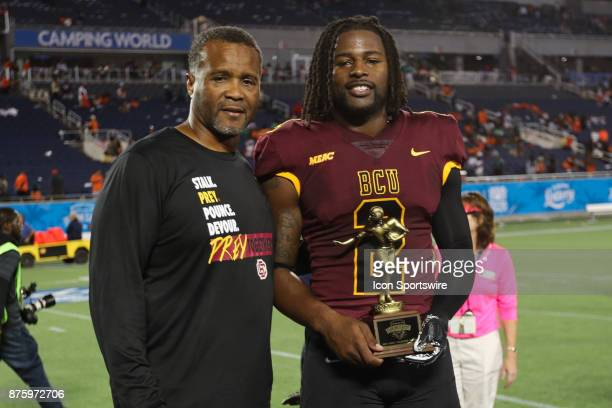 Bethune Cookman Wildcats head coach Terry Sims and Bethune Cookman Wildcats quarterback Larry Brihm Jr pose with the winning team MVP Trophy after...