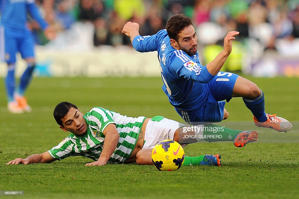 Betis' Chilean midfielder Lolo Reyes (L) vies with Real Madrid's defender Daniel Carvajal during the Spanish league football match Real Betis vs Real Madrid on January 18, 2014 at the Benito Villamarin stadium in Sevilla.
