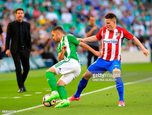 Betis' Danish defender Riza Durmisi fights for the ball with Atletico Madrid's French forward Kevin Gameiro during the Spanish league football match...