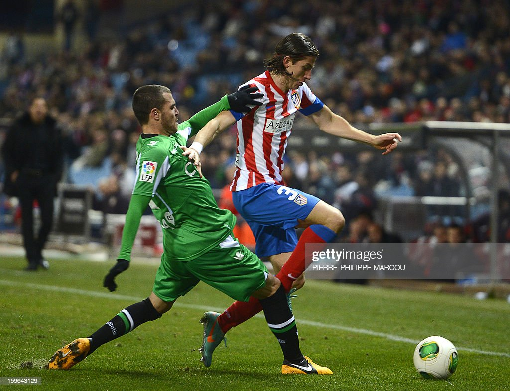 Betis' defender Javier Chica (L) vies with Atletico Madrid's Brazilian defender Filipe Luis during the Spanish Copa del Rey (King's Cup) quarter-final first leg football match Club Atletico de Madrid vs Real Betis at the Vicente Calderon stadium in Madrid on January 17, 2013.