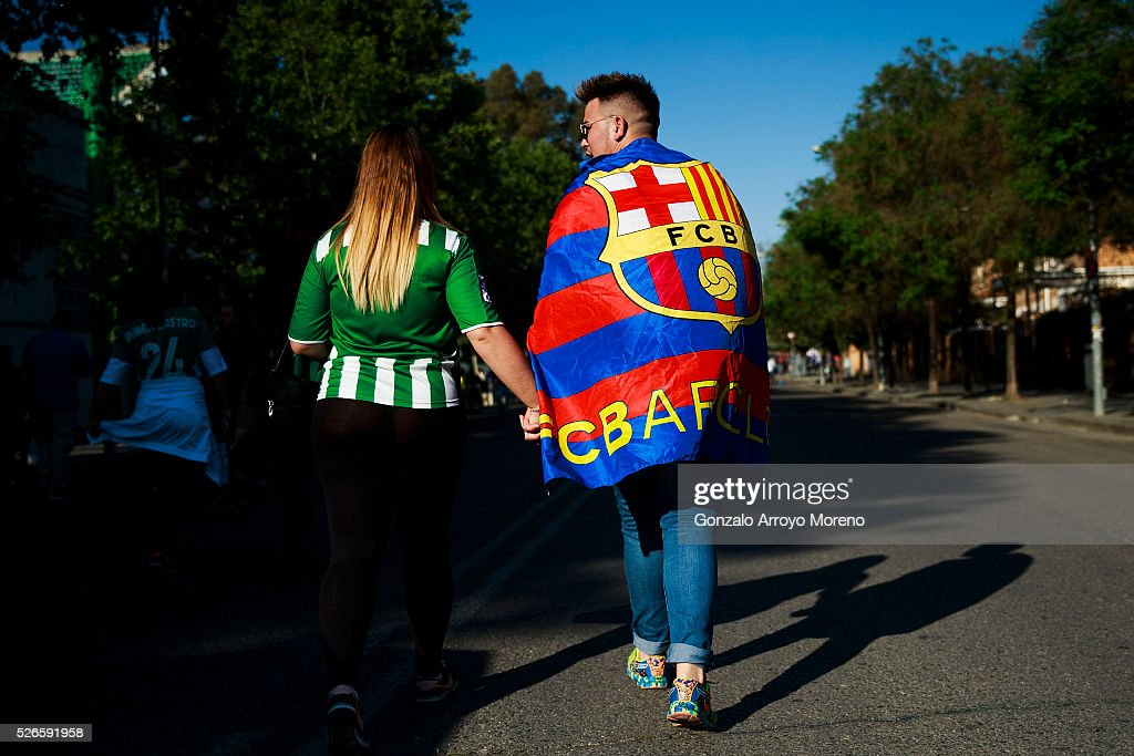 A Betis fan and a FC barcelona one walk together at Estadio Benito Villamarin outdoors before the La Liga match between Real Betis Balompie and FC Barcelona on April 30, 2016 in Seville, Spain.