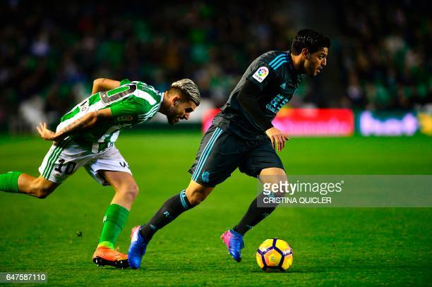 Betis' forward Dani Ceballos vies with Real Sociedad's Mexican forward Carlos Vela during the Spanish league football match Real Betis vs Real...