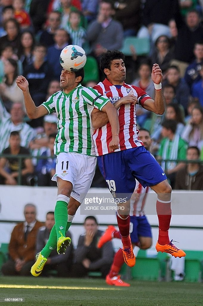 Betis' midfielder Juanfran vies with Atletico Madrid's Brazilian forward Diego da Silva Costa during the Spanish league football match Real Betis...