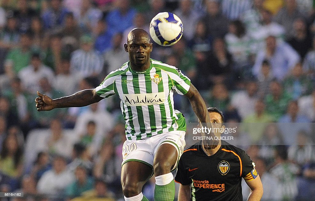 Betis's Achille Emana vies for the ball with Valencia's Carlos Marchena during their Spanish league football match at the Ruiz de Lopera stadium in...