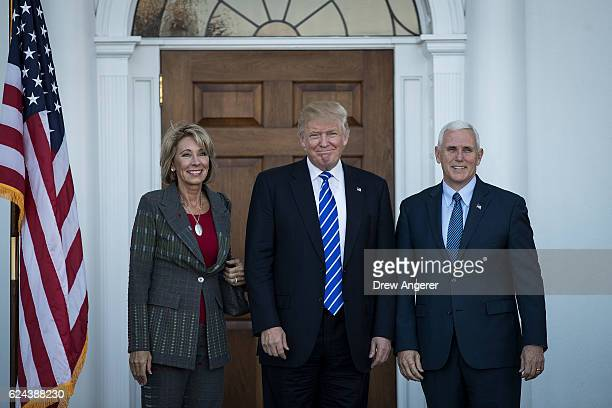 Betsy DeVos presidentelect Donald Trump and vice presidentelect Mike Pence pose for a photo outside the clubhouse at Trump International Golf Club...