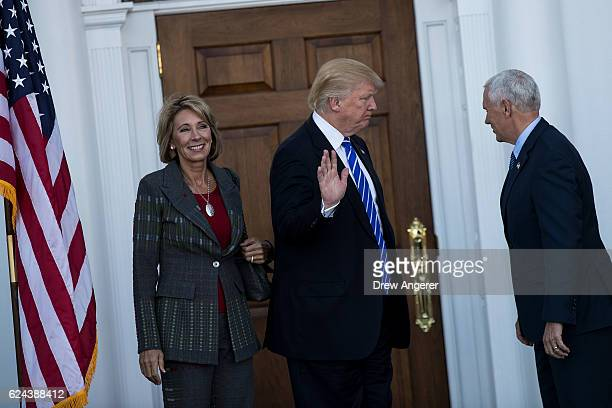 Betsy DeVos presidentelect Donald Trump and vice presidentelect Mike Pence prepare to head inside the clubhouse after posing for a photo at Trump...