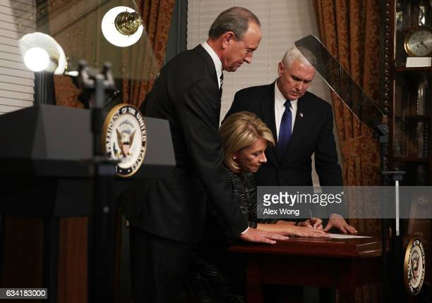 Betsy DeVos signs the affidavit of appointment as her husband Dick DeVos and Vice President Mike Pence look on during a swearingin ceremony at the...