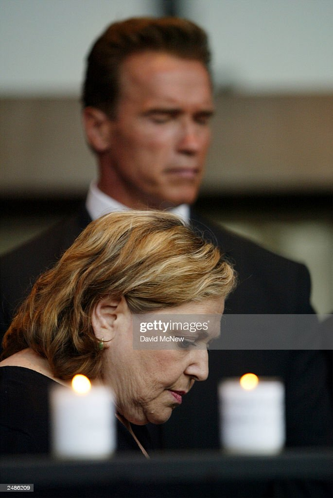 Betsy Golkin and California gubernatorial candidate <a gi-track='captionPersonalityLinkClicked' href=/galleries/search?phrase=Arnold+Schwarzenegger&family=editorial&specificpeople=156406 ng-click='$event.stopPropagation()'>Arnold Schwarzenegger</a> bow their heads in a moment of silence behind candles lit in honor of those who died in the September 11 terror attacks, including one for her nephew, at the Simon Wiesenthal Center September 11, 2003 in Los Angeles, California. Schwarzenegger is running to replace current governor Gray Davis in the October 7 recall election.