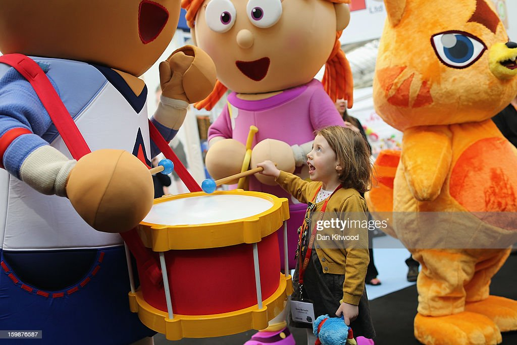 Betsy McCredie, 4, from Glasgow interacts with life size cartoon characters during the 2013 London Toy Fair at Olympia Exhibition Centre on January 22, 2013 in London, England. The annual fair which is organised by the British Toy and Hobby Association, brings together toy manufacturers and retailers from around the world.