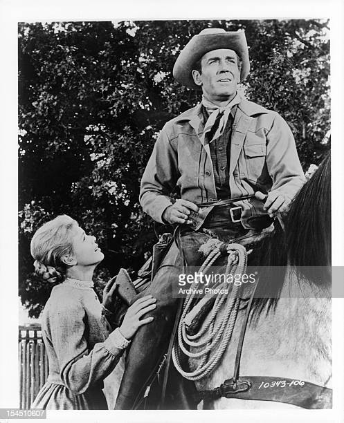 Betsy Palmer looks up to Henry Fonda on a horse in a scene from the film 'The Tin Star' 1957