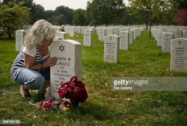 Betsy Reed Schultz sits consoled by friends at her son's gravesite Special Forces Capt Joseph W Schultz at Arlington Cemetery October 10 2011 Schultz...