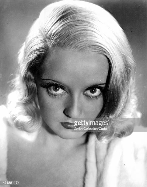Bette Davis headshot intense facial expression dark eye makeup and mascara harshly lit 1949