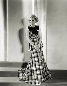 Bette Davis the chic young Warner Brothers player featured in Money Man introduces the pyramid silhouette in this smart plaid gingham frock Red white...