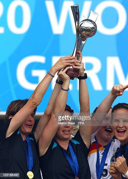 Bettina Wiegmann assistant coach and Maren Meinert head coach of Germany lift the trophy after winning the 2010 FIFA Women's World Cup Final match...