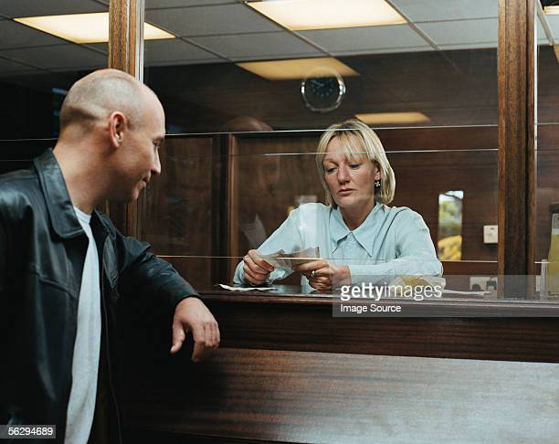 Betting shop worker counting money for customer
