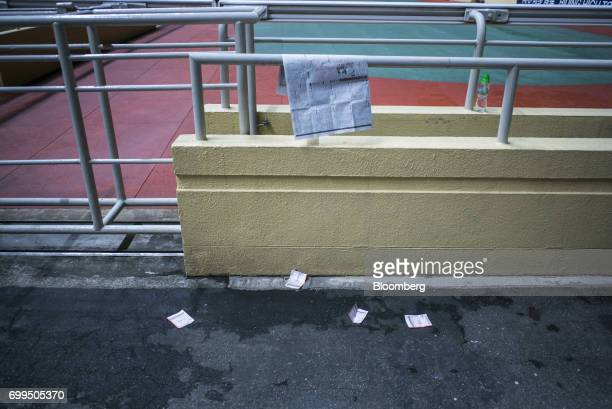 Betting slips sit on the ground after races at the Hong Kong Jockey Club's Happy Valley racecourse in Hong Kong China on Wednesday June 14 2017 One...