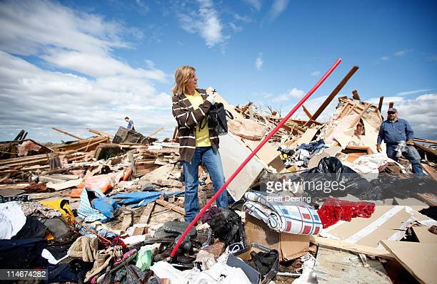 Betty Beaulac finds a cross in the debris of her friend Beth Parrett's house struck by a tornado May 25 2011 in Piedmont Oklahoma The state medical...
