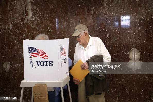 Betty Carlson helps her husband Keith Carlson who is visually impaired fill out his ballot during early voting at the Black Hawk County Courthouse on...