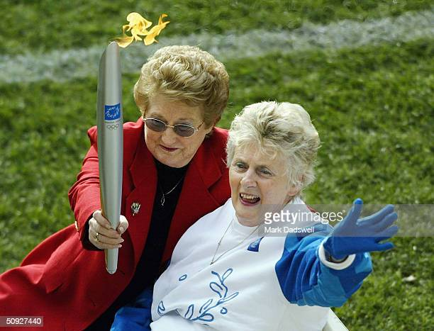 Betty Cuthbert former Olympian waves to the crowd during the torch relay at half time of the round eleven AFL match between the Hawthorn Hawks and...