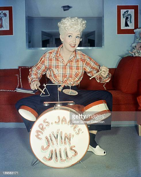Betty Grable US actress dancer and singer wearing a plaid shirt sitting behind a child's drum kit which has 'Mrs James Jivin' Jills' written on the...
