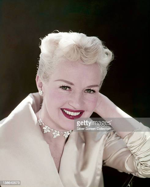 Betty Grable US actress dancer and singer wearing a white jacket with a floral motif choker around her neck in a studio portrait against a black...