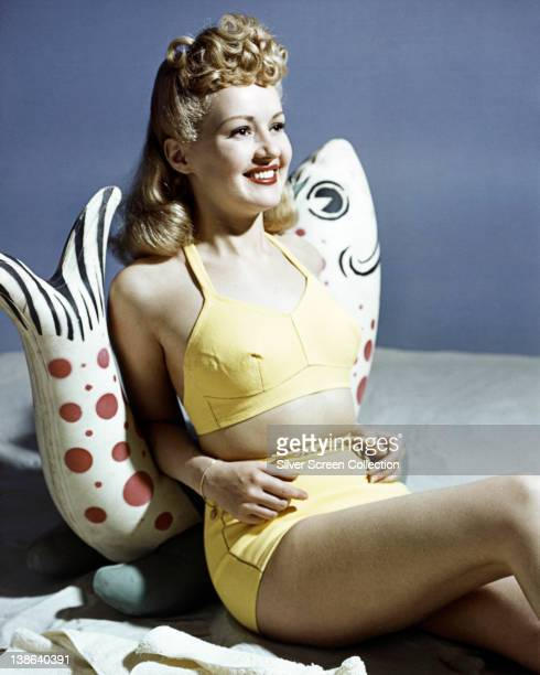 Betty Grable US actress dancer and singer wearing a yellow bikini as she leans against a fish ornament in a studio portrait against a grey background...