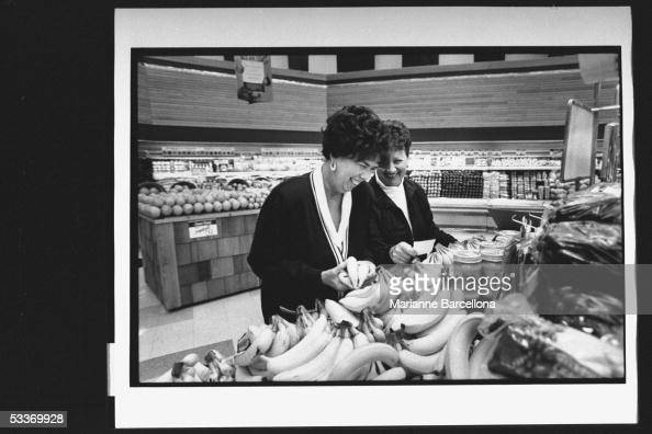 Betty Janko recipient of kidney from donor Amy Federici who was victim in LIRR massacre holding bunch of bananas as she grocery shops in produce...