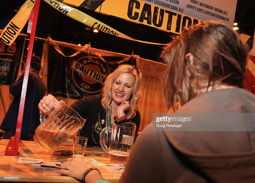 Betty Wang of Caution Brewery in Denver, Colorado pours beer for a festival goer during the 32nd annual Great American Beer Festival at the Colorado Convention Center on October 10, 2013 in Denver, Colorado. The GABF runs October 10-12 and 49,000 attendees will be offered 3100 beers from 624 breweries.