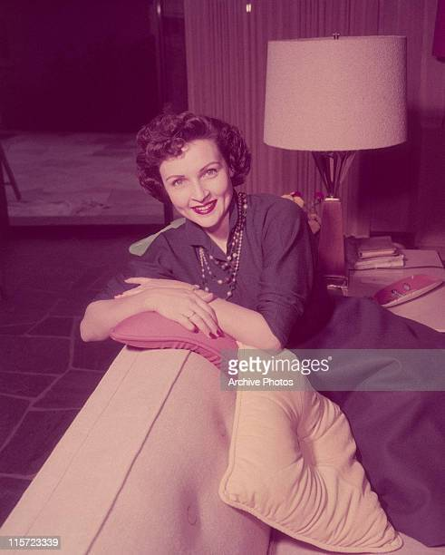 Betty White US actress and comedian smiling while sitting with her arms folded across a pillow on the backrest of a sofa in a living room circa 1955