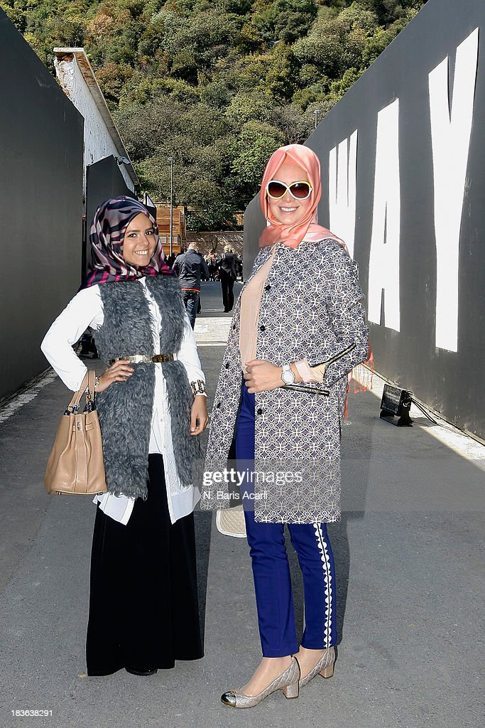 Betul Kahraman (L) wears a Ipekyol top, Sofia Baldi shoes, Hermes bag and a Carvella scarf, Tugba Saracoglu wears Beymen Club jacket and top, Fashion pants, Tory Burch shoes and a Versace bag during Mercedes-Benz Fashion Week Istanbul s/s 2014 presented by American Express on October 7, 2013 in Istanbul, Turkey.