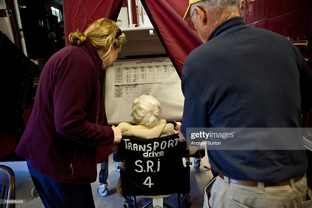 Bety Etzel (C) is helped into the voting booth in Bay Head Fire Station 14 on November 6, 2012 in Bay Head, New Jersey. As the New Jersey coastline continues to recover from Superstorm Sandy, numerous polling stations have had to be merged and relocated due to storm damage and power outages.