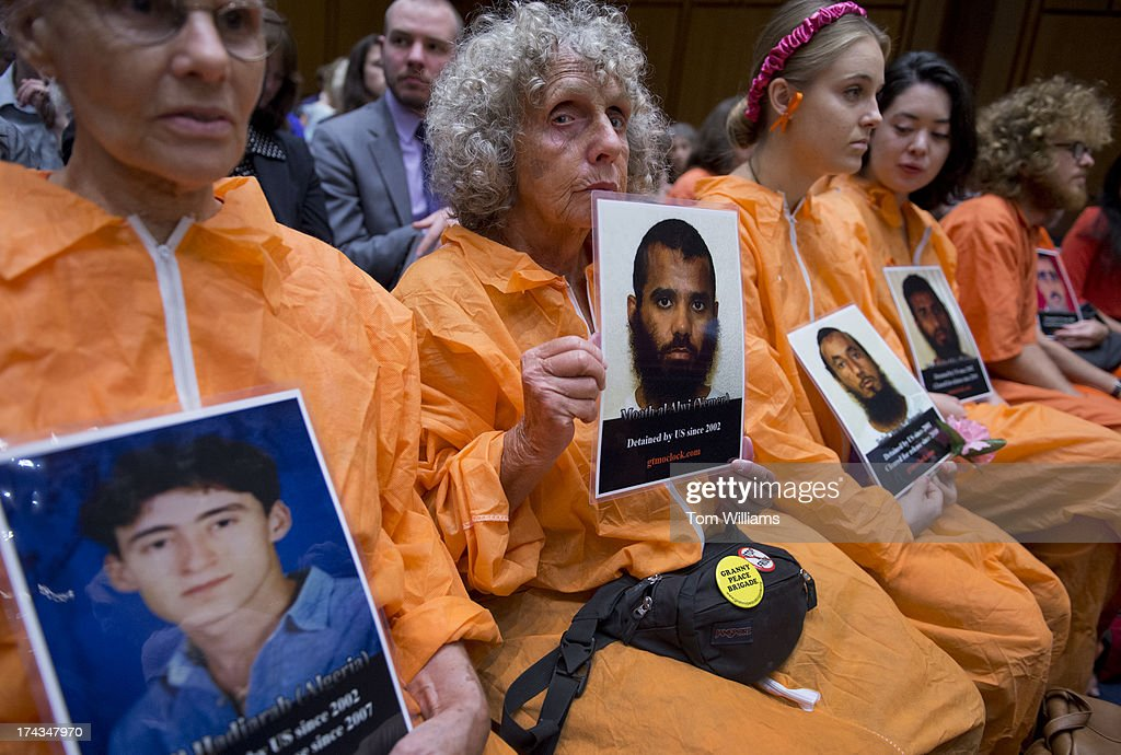 Bev Rice, second from left, of New York City, and others hold pictures of detainees during a Senate Judiciary Constitution, Civil Rights & Human Rights Subcommittee hearing in Hart Building to examine the closing of the Guantanamo Bay detention camp focusing on the 'national security, fiscal and human rights implications.'